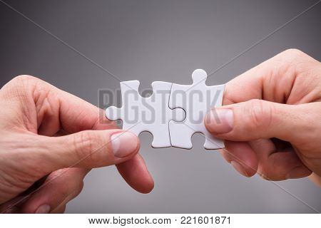 Close-up Of Businesspeople Holding White Jigsaw Puzzle On Grey Background