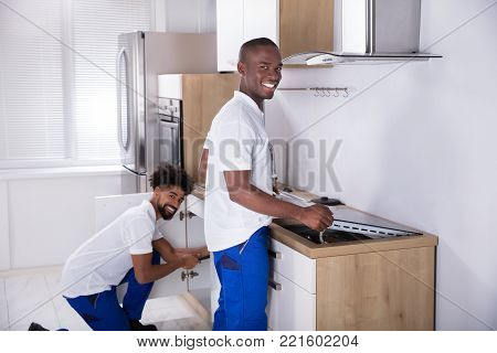 Two Young Handy Men In Uniform Fixing Induction Stove And Sink Pipe In The Kitchen
