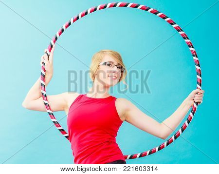 Fitness, activity, healthy lifestyle. Young blond woman doing exercise with hula hoop, on blue
