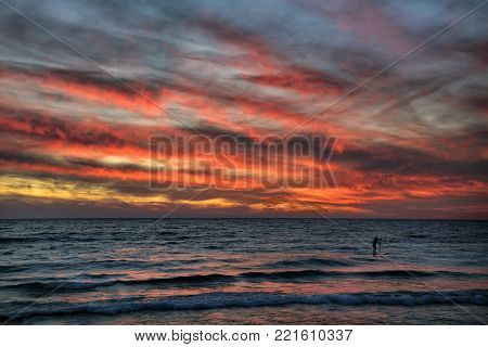 Stand-up paddleboarder surfing the waves of Lake Michigan at the public beach in Frankfort, Michigan under a dramatic sunset. USA