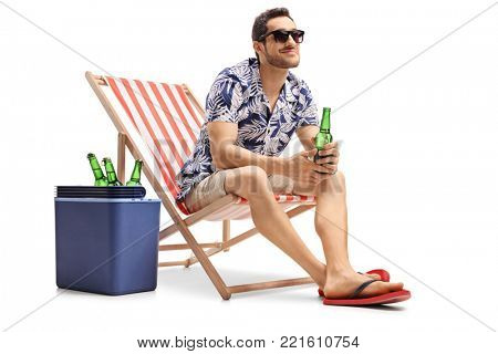 Tourist with a beer bottle sitting in a deck chair next to a cooling box and looking away isolated on white background