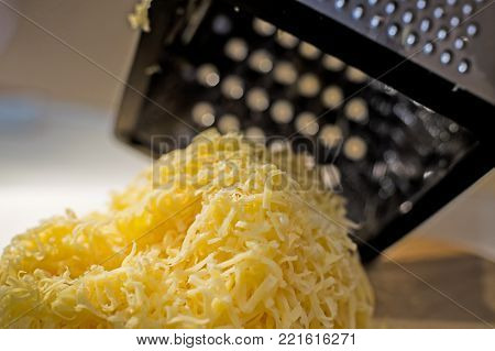 A pile of grated yellow fresh cheese on a wooden board against the background of a steel grater for cheese. Close view. Still life.