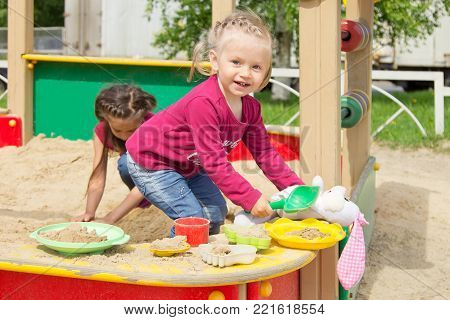 Adorable little girl playing in the sandbox on a playground