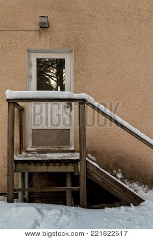 The snow has covered the wooden stairs leading to the door of an old building in the Northern Finland.