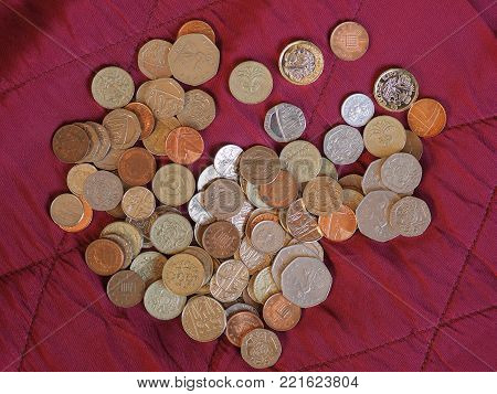 Pound coins money (GBP), currency of United Kingdom over crimson red velvet background