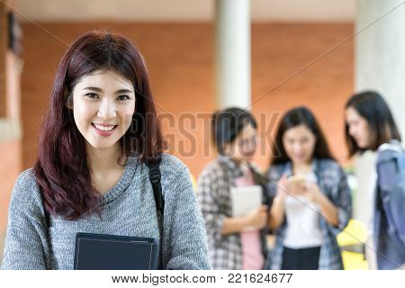 Portrait smilling and happy asian college student at campus with group of student talking background. Education at university concept.