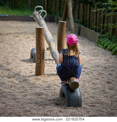 lonely little girl alone on a playground