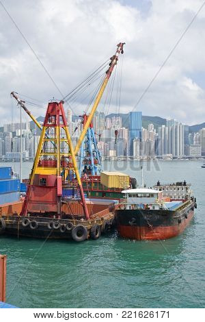 Container being swung from lighter to dockside by large derrick. High density apartments of Hong Kong Island in background.