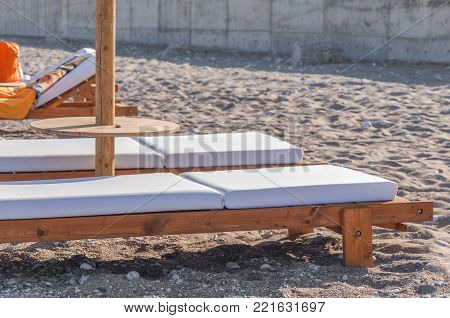 Two Empty Sun Bed At Small Pebble Stone Beach For Relaxation