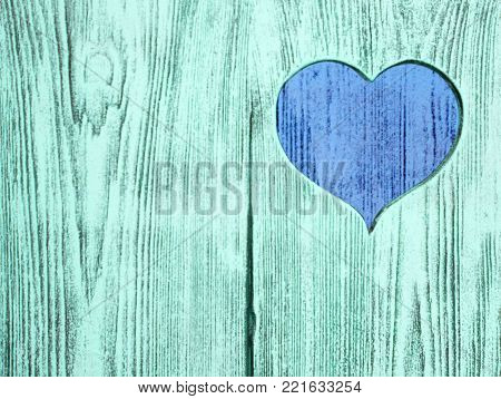 blue heart carved in a wooden board. Background. Postcard, valentine