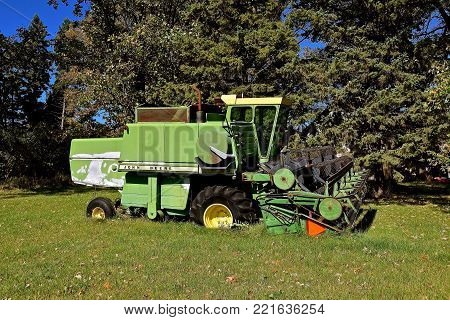 DETROIT LAKES, MINNESOTA, Sept 26, 2017: The faded self propelled John Deere combine left for salvage is a product of John Deere Co, an American corporation that manufactures agricultural, construction, forestry equipment, machinery, and diesel engines,