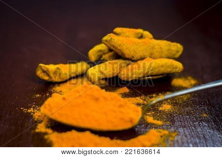 Turmeric,curcuma Longa And Its Powder On A Wooden Surface.