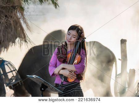 Thai women wear Thai traditional Thai dress, rural Thai culture, and violin in the countryside.