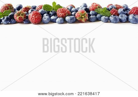 Black-blue and red berries. Ripe raspberries, blueberries with mint on white background. Berries at border of image with copy space for text. Background berries. Various fresh summer berries isolated on a white.