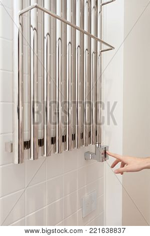The man hand regulates the temperature in the heated towel rail.