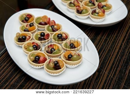 Dessert table. Deserts isolated on dark background, decorated plate, snack, snack food on