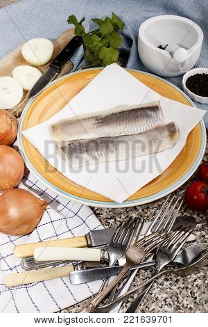 fresh herring fillet on a plate with a kitchen paper towel