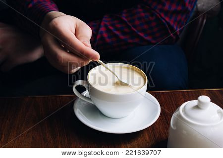 coffee in hands. woman relaxing near the window in a vintage restaurant. caffeine is invigorating. cappuccino in a glass