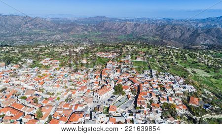 Aerial bird eye view of famous landmark tourist destination valley Pano Lefkara village, Larnaca, Cyprus. Ceramic tiled house roofs, greek orthodox church at south troodos hills, kionia, from above.