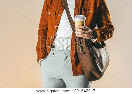 partial view of man in stylish clothing holding coffee to go isolated on beige