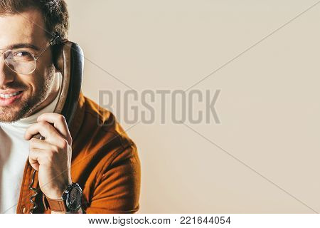 partial view of smiling man talking on telephone isolated on beige