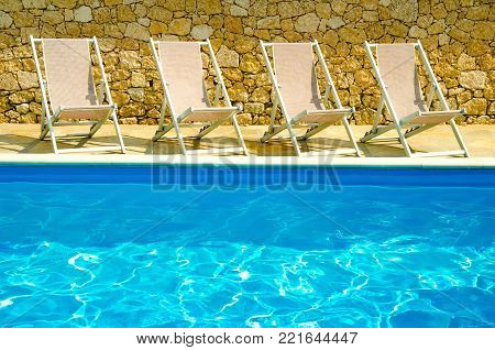 a pool with chaise-longues in a hotel