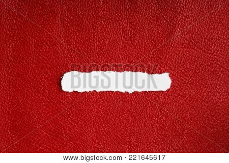 Piece scrap of white torn or ripped paper banner, blank copy space for text message on red leather background