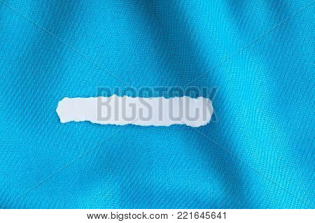 Blank copy space scrap of paper on blue background cloth wavy folds of textile texture material