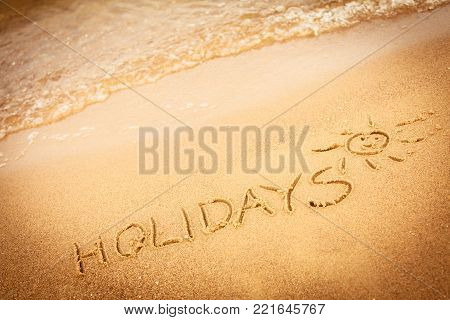Summer vacation concept. The word holidays written in the sand on beach.