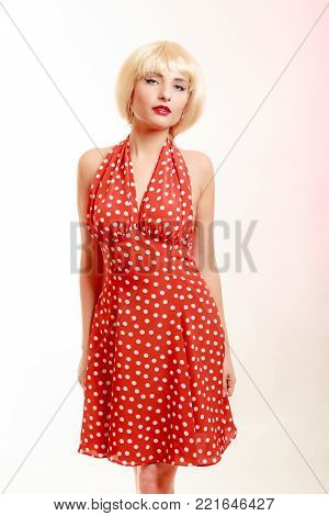 Vintage pinup style. Portrait of beautiful stylized young woman. Attractive girl in blond wig and retro spotted red dress on pink. Disguise. Studio shot.