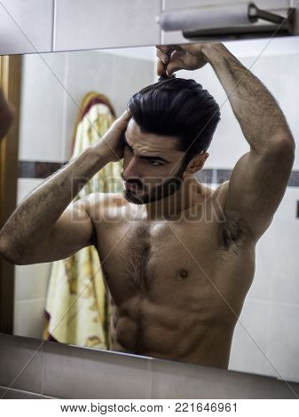 Shirtless Handsome Young Man Brushing and Combing Hair in Mirror Getting Ready to Go Out