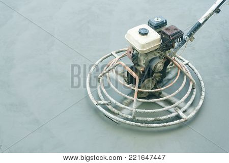 Power trowel machine for smoothing surface to finish of concrete slab floor work step of the building construction. Construction work concept.
