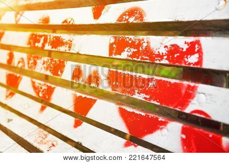 Red hearts painted on a white wooden bench in diagonal view with golden glow from the sun. Love concept.