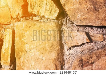 Close up of large glossy stones in wall as background with copy space and golden glow from the sun. Diagonal view.