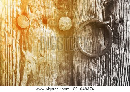 Old rustic weathered wooden door with a wrought iron ring handle and large old studs or nails, close up background texture with golden glow from the sun.