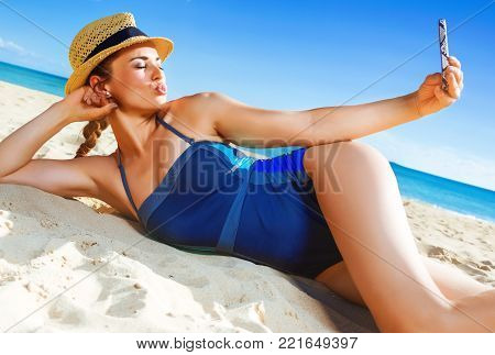 Sun kissed beauty. healthy woman in swimsuit on the beach with smartphone taking selfie