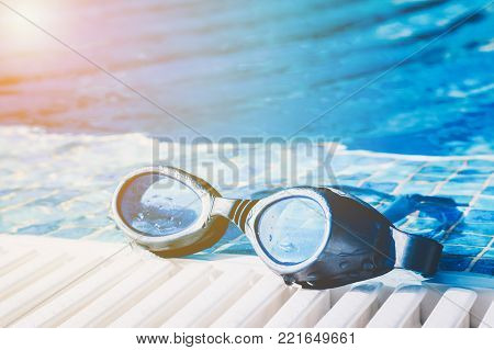 Image of a swimming pool goggles on the poolside with golden glow from the sun.