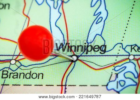 Close-up of a red pushpin on a map of Winnipeg, Canada.