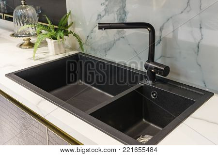 Black kitchen sink and Tap water in the kitchen. The interior of the kitchen room of the apartment. Built-In Appliances. Kitchen Appliance. Domestic Appliances