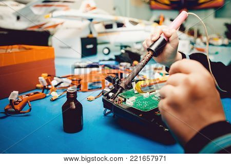 Man holds soldering iron, constructs automodels, solder schemes, assemble model on radio control
