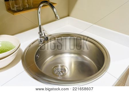 Stainless steel kitchen faucet and sink with light countertop