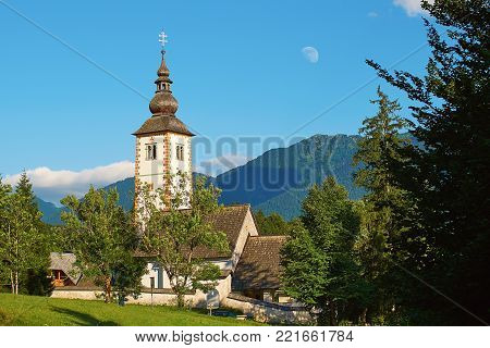 Church of St John the Baptist in Ribcev Laz, Slovenia located on the shore of lake Bohinj with a daytime moon over it poster