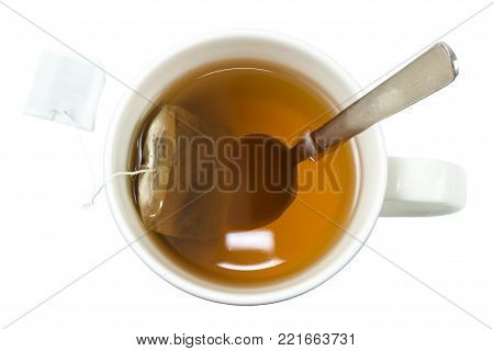 Close-up of a cup of tea with a teabag and a spoon viewed from directly above, isolated on white background.