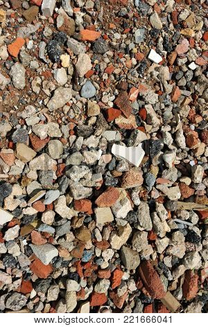 Recycled house demolition rubble that has been used as the base of a car park. It could be used as a background. Contains crushed bricks, concrete and a white piece of a sink.