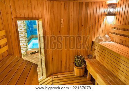 relaxation, harmony, weekends concept. there is comfortable room of steam bath with special set of things for rest there such as hats and brooms placed on the benches with door to the pool