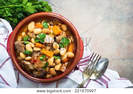 Beef stew with beans and vegetables in clay dish. Chili con carne. Top view copy space.