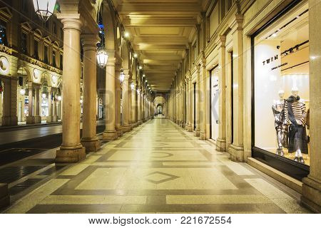 Turin, Italy, december 2017: night view of the traditional Portico in Via Roma in Turin with incidental people in the background