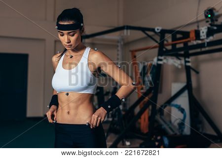 Portrait of runner wearing mask on treadmill in sports science laboratory. Sports man running on treadmill and monitoring his fitness performance.