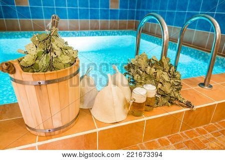 weekends, spa, holidays concept. there is popular set for having fun and rest in steam bath with friends, it is composed of brooms, wool hats, ice bucket and three glasses of beer