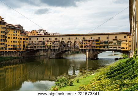 View on famous Ponte Vecchio bridge from the banks of the Arno river in Florence, Italy